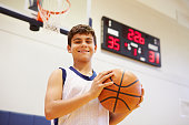Portrait Of Male High School Basketball Player Holding Basketball