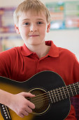 Portrait Of Male High School Pupil Playing Guitar