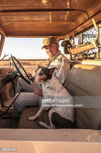 Portrait of male hunter and dog sitting in vehicle, Windhoek, Namibia, Namibia