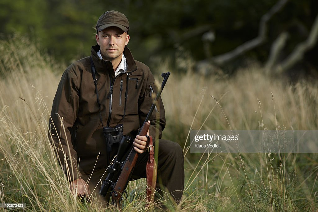 Portrait of male hunter with rifle