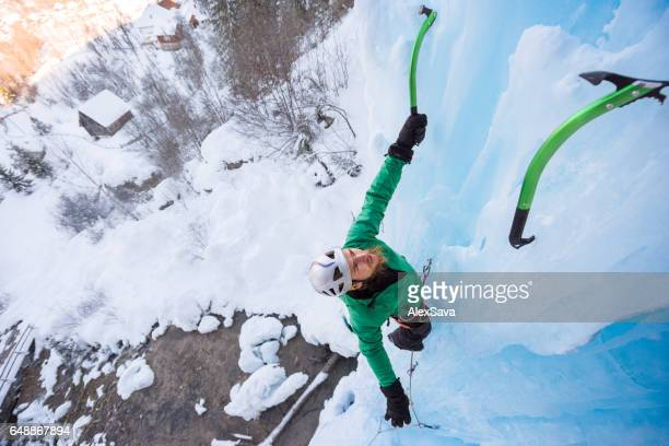 Portrait of male ice climber ascending on frozen waterfall