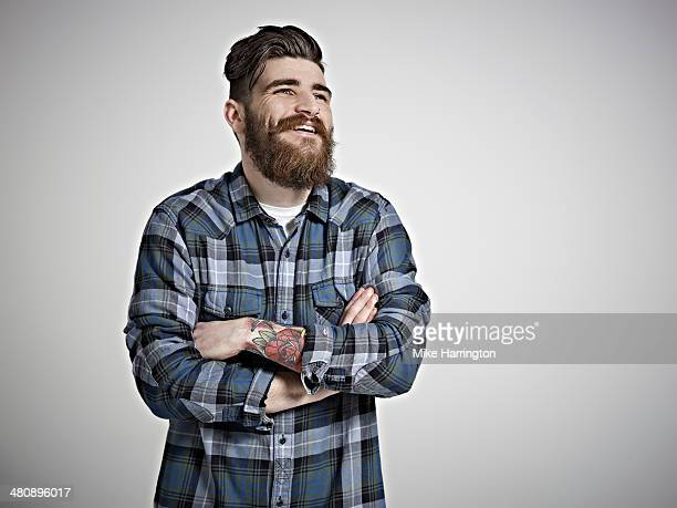 Portrait of male in check shirt laughing.