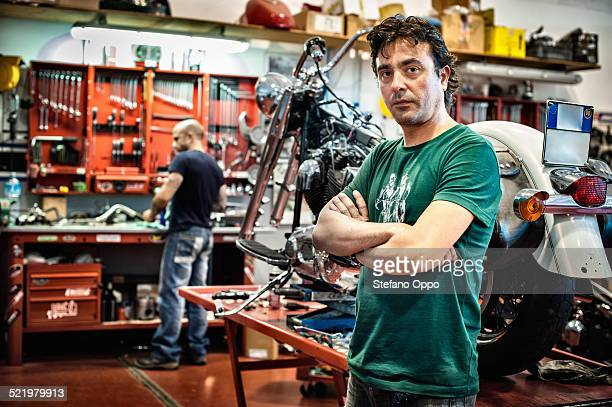 Portrait of male mechanic in motorcycle workshop
