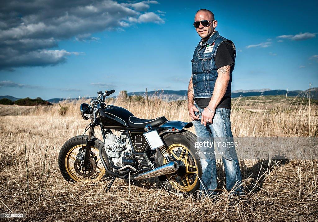 Portrait of male motorcyclist in plain landscape, Cagliari, Sardinia, Italy