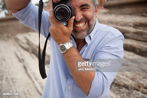 Portrait of male photographer using digital SLR camera, Ipanema beach, Rio De Janeiro, Brazil