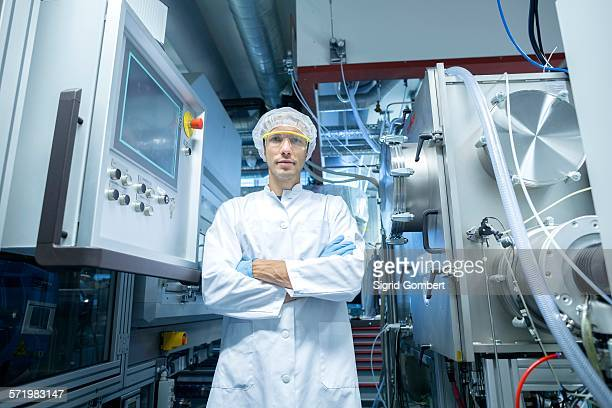 Portrait of male scientist with arms folded in lab cleanroom