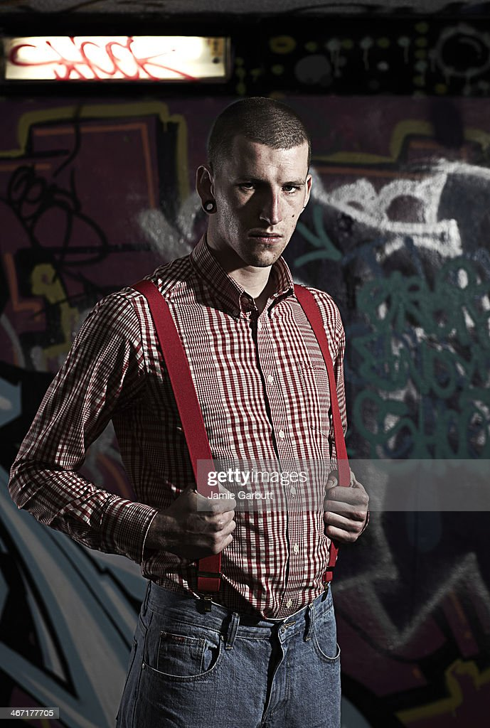 Portrait of male skinhead against graffitied wall : Stock Photo