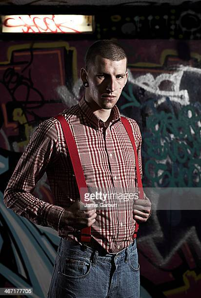 Portrait of male skinhead against graffitied wall
