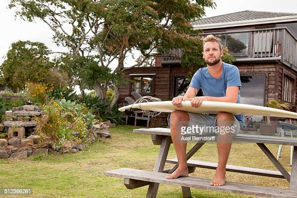 Portrait of male surfer sitting on picnic bench with surfboard on lap