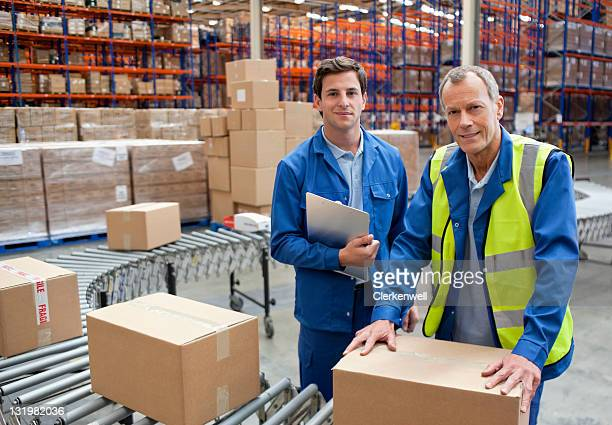 Portrait of male warehouse workers near conveyor belt