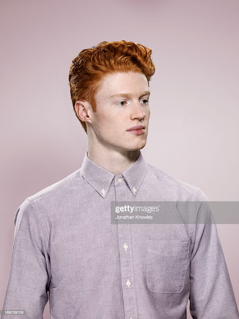 Portrait of male with wavy red hair, looking away : Stock Photo