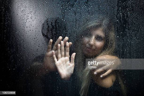 Portrait of Man and Woman Behind Wet  Window