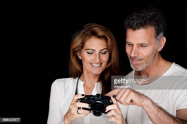 Portrait of man and woman looking at camera in front of black background