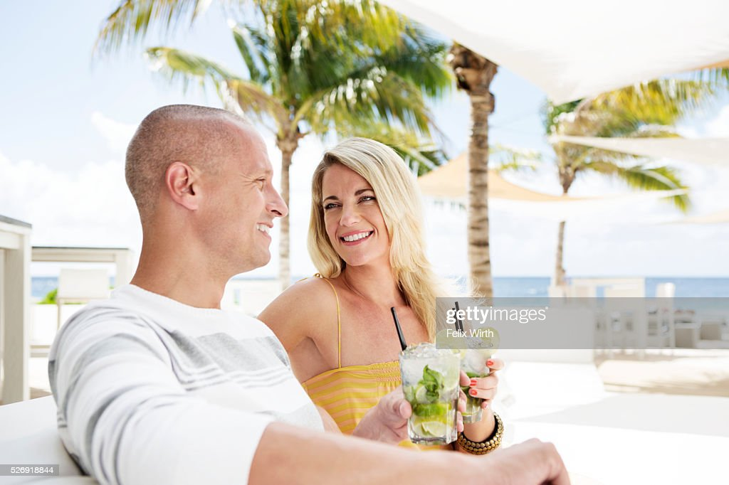 Portrait of man and woman relaxing at cafe nearby beach : Stock Photo