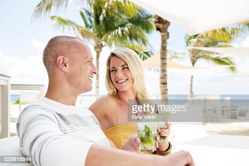 Portrait of man and woman relaxing at cafe nearby beach : Stock-Foto