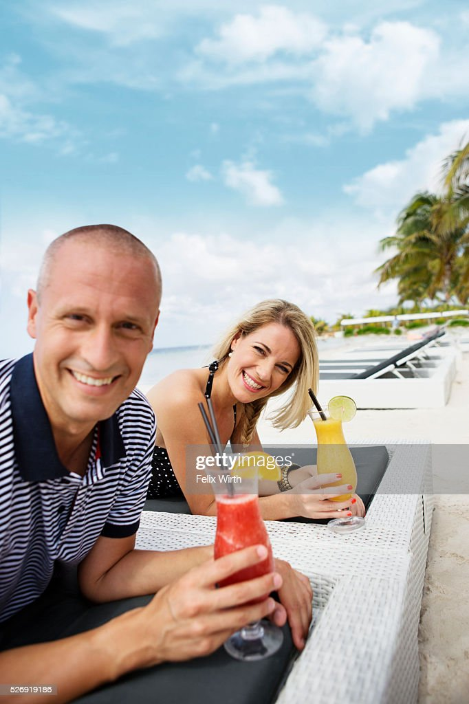 Portrait of man and woman relaxing on beach : Photo