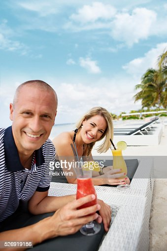 Portrait of man and woman relaxing on beach : Stock Photo