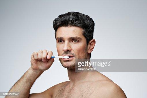 Portrait of man brushing teeth : Stock Photo