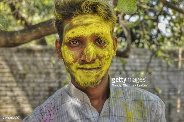 Portrait Of Man Covered With Yellow Face Powder During Holi Festival