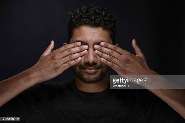 Portrait of man covering eyes with his hands