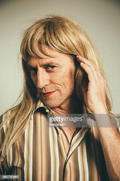 Portrait of man cross-dressed as blond woman
