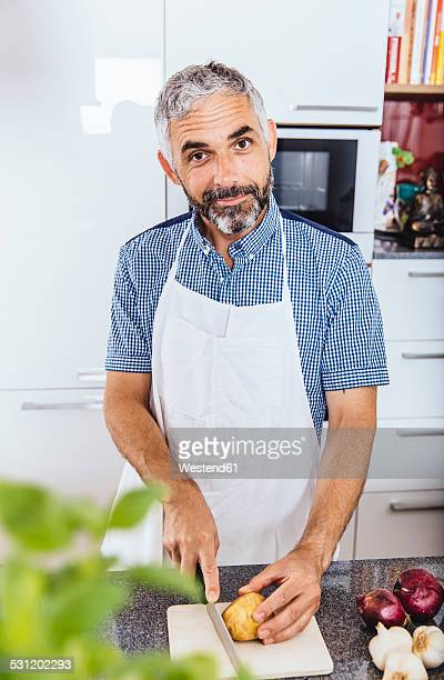 Portrait of man cutting potato in his kitchen