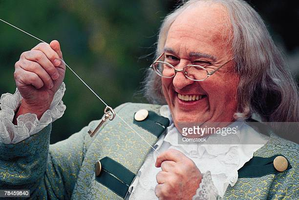 Portrait of man dressed as Benjamin Franklin with key and kite