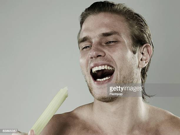 Portrait of man eating celery