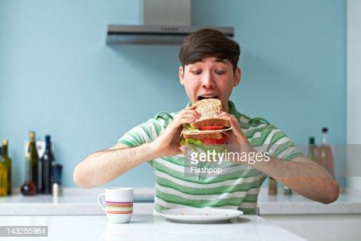 Portrait of man eating giant sandwich