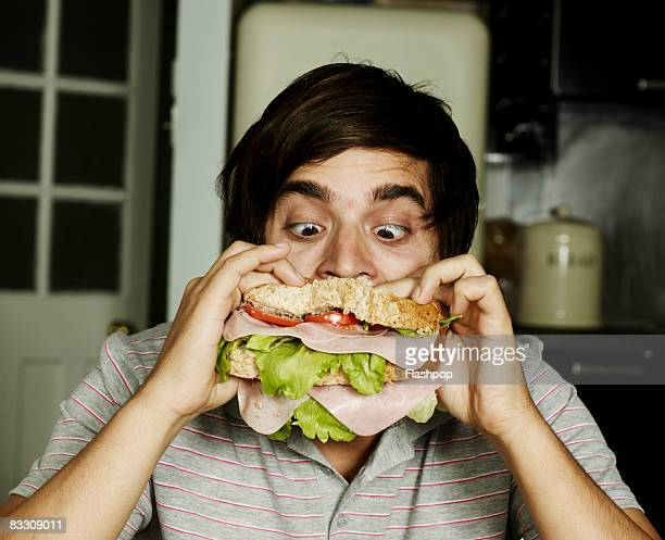 Portrait of man eating sandwich