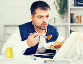 Portrait of man eating vegetable salad at laptop and documents at table