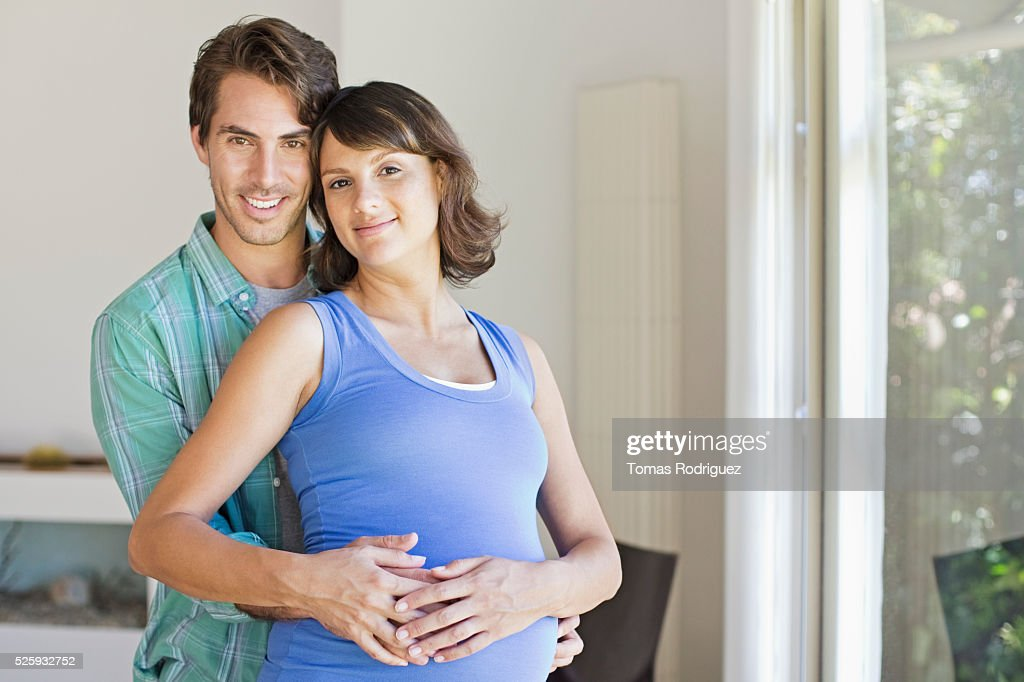 Portrait of man embracing pregnant woman : Stock Photo