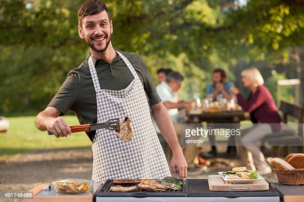 Portrait of man grilling meat at barbecue outdoors