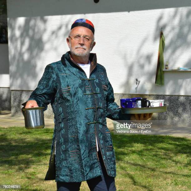 Portrait Of Man Holding Coffee Cups In Plate While Standing On Field