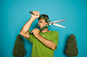 Portrait of man holding hedge clippers in front of face