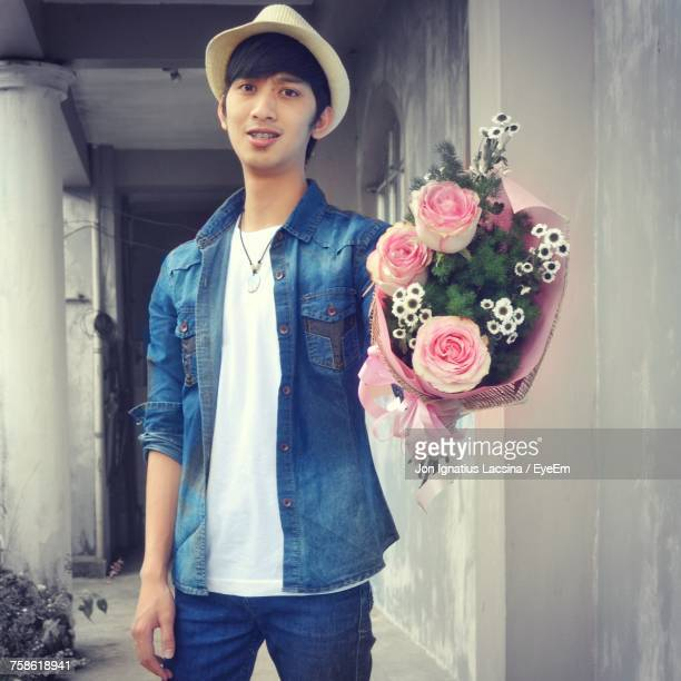 Portrait Of Man Holding Roses Bouquet While Standing Against Wall