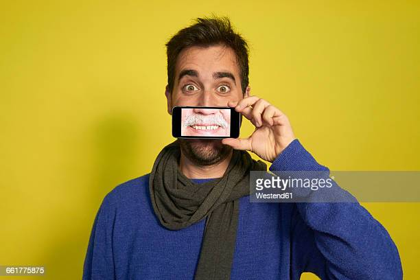 Portrait of man holding smartphone with photography of another mans smiling mouth