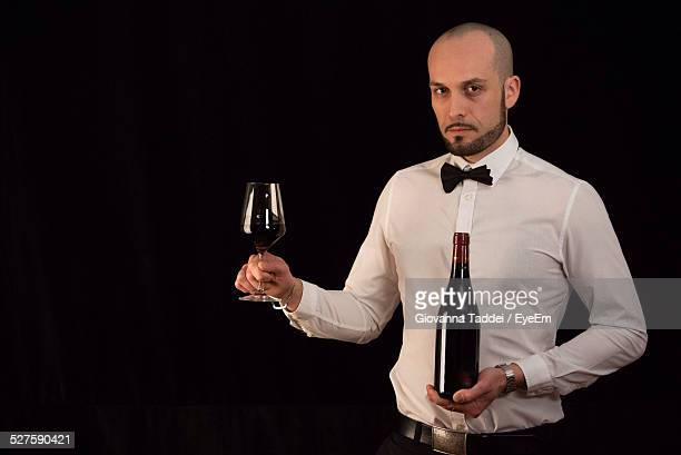 Portrait Of Man Holding Wine Bottle And Glass Against Black Background