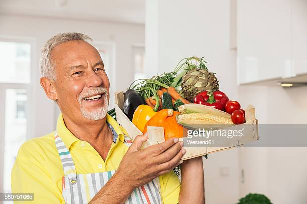 Portrait of man holding wooden box of vegetables