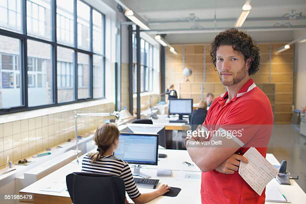 Portrait of man in busy creative office