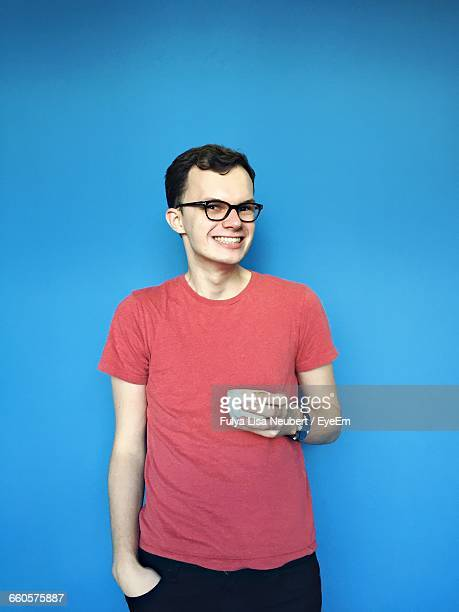Portrait Of Man In Eyeglasses Holding Cup Against Blue Background
