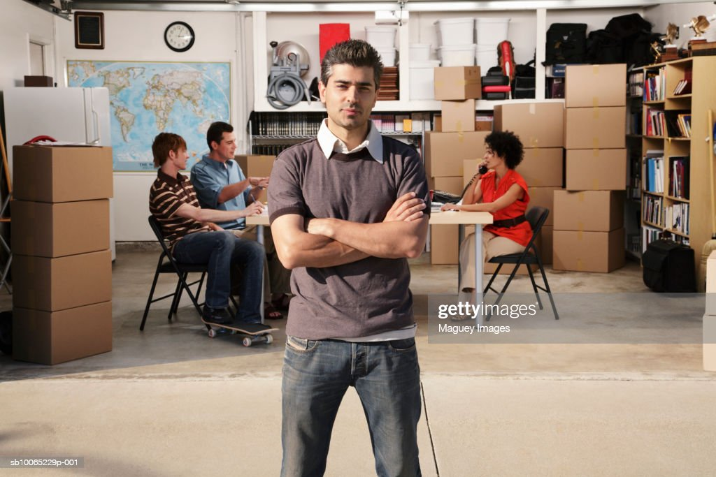 Portrait of man in front of garage, three people talking inside in background : Stock Photo