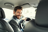 Handsome man in his car driving and facing camera