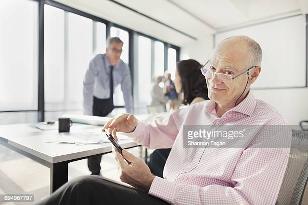 Portrait of man in meeting room with colleagues