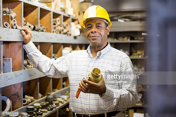 Portrait of man in plumbing stockroom holding products