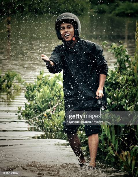 Portrait Of Man In Raincoat Standing At River During Rainy Season