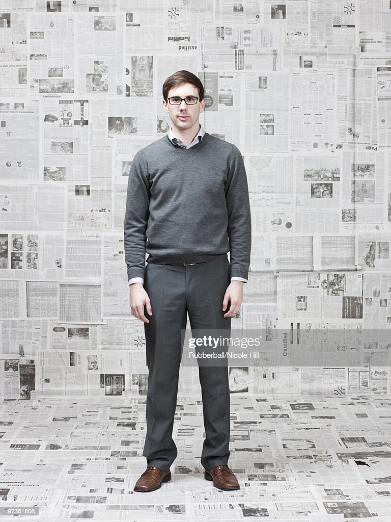 Portrait of man in room with walls covered with newspapers : Stock Photo
