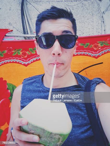 Portrait Of Man In Sunglasses Drinking Coconut Water Against Fabric