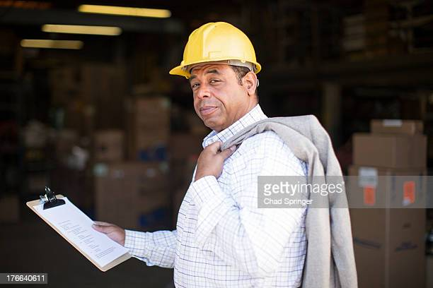 Portrait of man in warehouse with clipboard