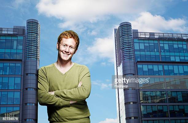 Portrait of man leaning against office building